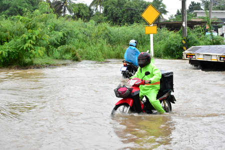 Food rider or food delivery rider is riding his motorcycle through the way which fulled with floodwater, concept for safety, insurance, work from home