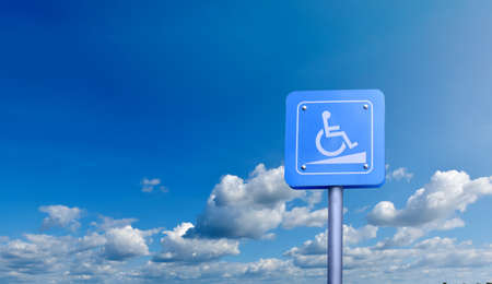 Disabled sign on pole with cloudy blue sky background.