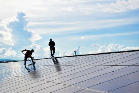The workers from the photovoltaic company are washing and cleaning the surface of the photovoltaic system which installed on the roof of the building to get better energy from the sunlight. Archivio Fotografico