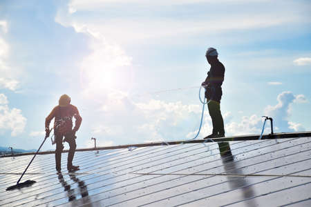 The workers from the photovoltaic company are washing and cleaning the surface of the photovoltaic system which installed on the roof of the building to get better energy from the sunlight.