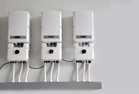 Photovoltaic system converters installed on the wall of the building to control and lead the electric to rooms inside the building, concept for using renewable and sustainable power from the sunligh.