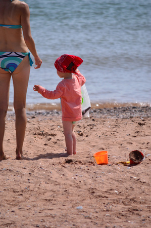 bathing costume: Female in small two-piece bikini, with little girl on beach, a delightful scene