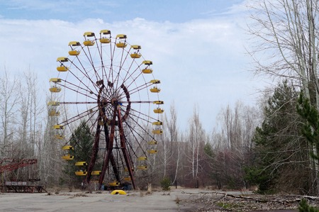 pripyat: Group of tourists in abandoned childrens park in Pripyat, Chernobyl. In front of the Ferris wheel. Stock Photo