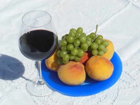 Still life with fresh peaches, some grape and glass of red wine photo