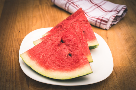 glanz: Watermelon slices on the white porcelain plate, served with napkin, straw-coloured wooden background