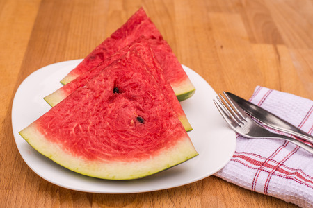 glanz: Watermelon slices on the white porcelain plate, served with cutlery napkin, straw-coloured wooden background Stock Photo