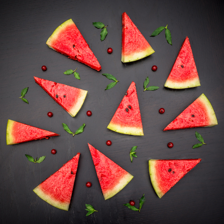 glanz: Slices of fresh jucie red watermelon on black background. Decorated with mint and wineberry. Stock Photo