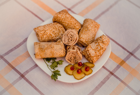 blini: Tasty pancakes with meat on white plate closeup. Crepes stuffed with finely cut meat. Stock Photo