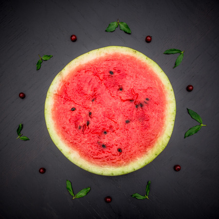 glanz: A half of fresh jucie red watermelon on black background. Decorated with mint and wineberry. Stock Photo