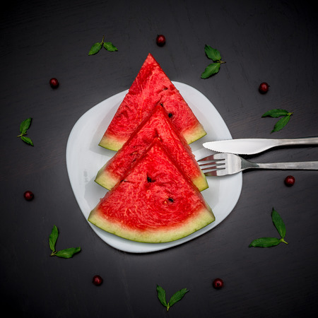 glanz: Slices of fresh jucie red watermelon on the white plate served with fork and knife. Decorated with mint and wineberry on black background. Stock Photo