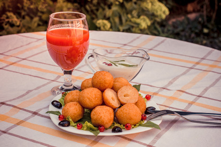 Hot juicy fried cheese balls with sauce on a white plate. Glass of tomato juice. Stock Photo