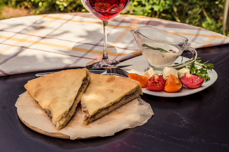 Delicious rustic crispy pie with meet and herbs. Served on wooden plate, surrounded by glass of red wine, white sauce and vegetables. Caucasian, greek, mediterranean cuisine. Healthy diet    lunch, breakfast or snack.