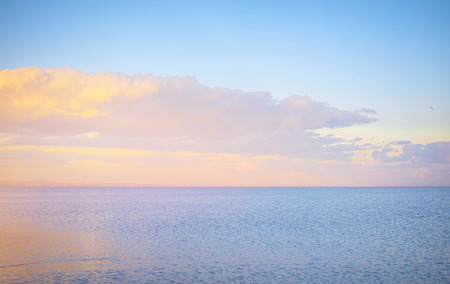 azov: Sky background on sunset, seafront. Nature composition. Panoramic sunset sky background. Taganrog Bay, Azov sea. Beautiful sunset over sea with reflection in water, majestic clouds in the sky.