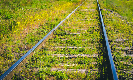 Overgrown abandoned railroad track. Railroad abstract conceptual photo. Detail of Railway railroad tracks for trains vintage.