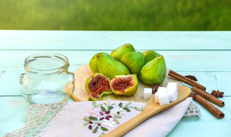 Fresh green figs, jam cooking process. Still life with figs on a wooden background, surrounded by spices, embroidered napkin, vintage spoon.