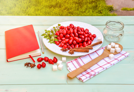 Fresh red cornel berries on white plate, prepearing for homemade cornelian cherry jam, surrounded by jelly jar, flax napkin, vintage spoon, sugar, spices, notebook for recipes, wooden background.