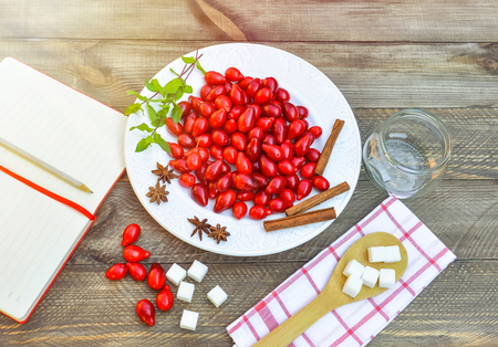 Fresh red cornel berries on white plate, preparing for homemade cornelian cherry jam, surrounded by jelly jar, flax napkin. Vintage spoon, sugar, spices, notebook for recipes, rustic wooden background.