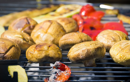 Grilling vegetables on chargrill. Barbecue. Cooking vegetables on the grill pan in a herb marinade, top view. Delicious vegetable barbecue on grill. 스톡 콘텐츠
