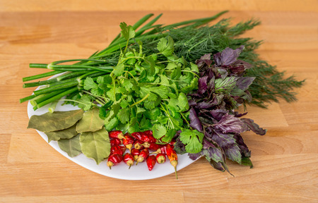 Close up of green organic herbs, basil, coriander, fennel, green onion, red chili peppers on white plate, rustic wooden background. Fresh herbs for Caucasian, Turkish, Mediterranean, Oriental cuisine.