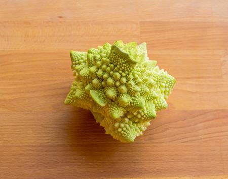 Romanesco broccoli, or Roman cauliflower. Romanesco green broccoli cabbage. Bright green autumn cabbage romanesco on a wooden board.