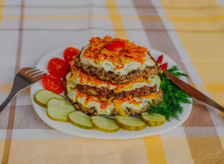 Pie of beef liver. Focus on the middle hepatic pie. Tomato, liver, onion, carrot and garlic, eggs are part of the recipe of the meat dishes. Liver pie on a background of vegetables.