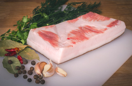 Fresh raw pork fat ready for gammoning on wooden cutting boards, spices and herbs. Whole uncooked pork fat prepare for salting. Large piece of fresh pork fat. Stock Photo