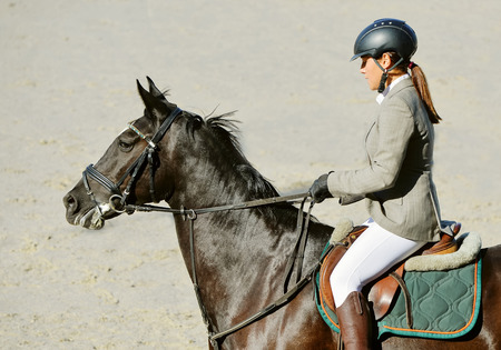 Black horse and girl in uniform Equestrian sport background.