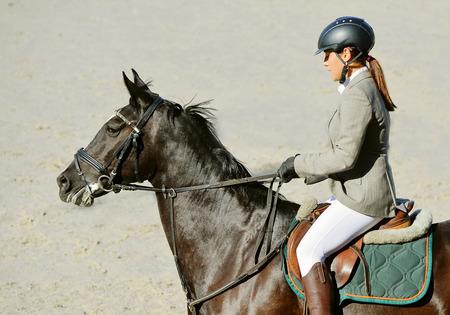 Black horse and girl in uniform Equestrian sport background. 版權商用圖片