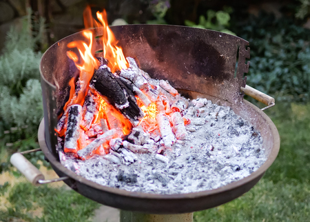 Flaming grill with open fire, ready for product placement. Summer or autumn charcoal, wood grilling, barbecue, bbq and party. Cooking heat from below.