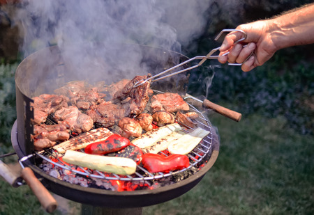 Cooking barbecue vegetables and meat. Chargrill. Close-up on the hand, grilling food on the marinade, top view. Delicious bbq on grill. 스톡 콘텐츠