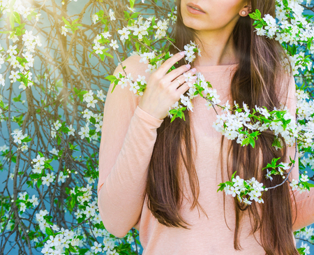 Beautiful girl with spring cherry flowers, sunshine backlit. Pretty young brunette woman's hand touching a blooming tree branches. Fashion, happiness and lifestyle concept.