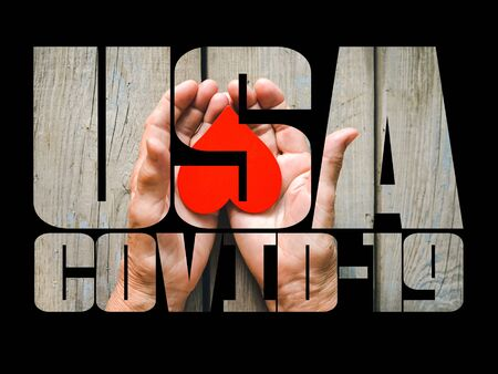 COVID-19 coronavirus. Fill text USA with old, young hands, red heart image cut. Elderly people health. Compassion, dangerous, volunteer, help, virus outbreak, stop sign, stay at home. Stock Photo