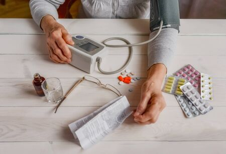 Senior wrinkled hands with blood pressure measure cuff, medicine bottle, glass, colorful pills, thermometer on a table. Old woman checking blood pressure on a tonometer. Elderly health care, old age. Stock fotó