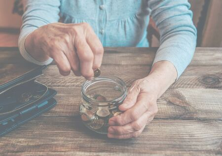 Old wrinkled hand holding jar with coins, empty wallet, wooden background. Elderly woman throws a coin into a jar, counting. Saving money for future, retirement fund, pension, poorness, need concept.