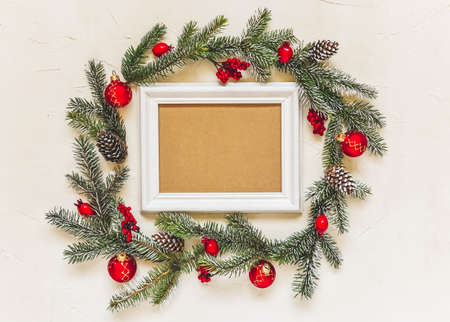 Christmas light background, fir branches wreath with red baubles and berries, beautiful frame and copy space for your text. White creative layout, flat lay, top view.