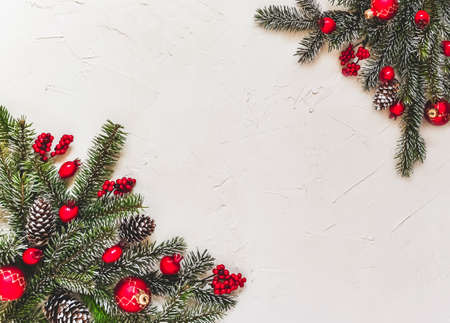 Christmas light background, fir branches with red baubles, pine cones and berries in the coner, beautiful frame and copy space for your text. White creative layout, flat lay, top view.