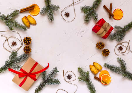 Christmas background, frame made of fir twigs, cones, berries. Christmas composition, decorated with pine tree branches, gifts, spices. Flat lay, top view, copy space.