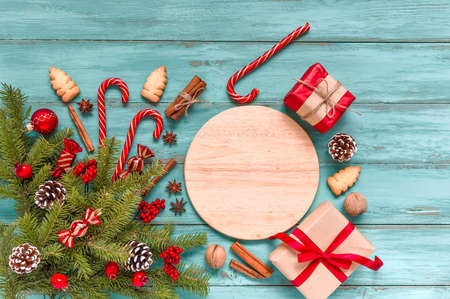Christmas table setting, menu composition, wooden blue background, pine tree branches, spices. Wooden round cutting board, frame made of fir twigs, cones, berries. Flat lay, top view, copy space. 免版税图像