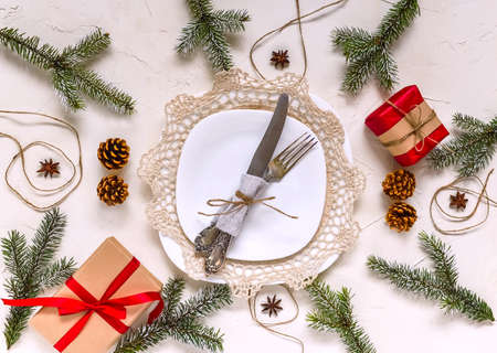 Christmas table setting, menu concept composition, decorated with pine tree branches, spices. Christmas light background, frame made of fir twigs, cones, berries. Flat lay, top view, copy space.