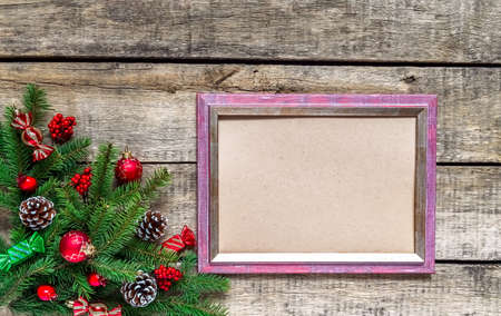 Christmas wood grunge background and frame for wishes. Top view, fir twigs, berries, baubles. Christmas, New Year decoration, pine tree branches and cones, light background, flat lay, copy space. 免版税图像