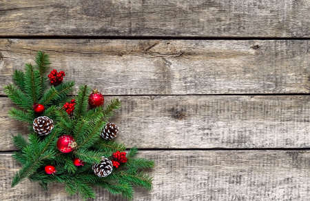 Christmas background, old wood texture, festive corner decorate. Pine fir leaf, cones, red golden balls, baubles, berries, candy, gift box. Xmas, New Year wallpaper, greeting card, top view flat lay.