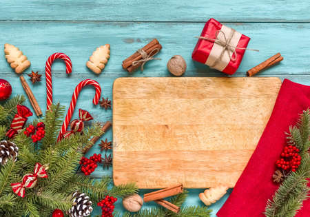 Christmas table setting, menu composition, wooden blue background, pine tree branches, spices. Wood scratched cutting board, frame made of fir twigs, cones, berries. Flat lay, top view, copy space. 免版税图像