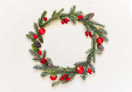 Christmas light background, fir branches with red baubles and berries, beautiful frame and copy space for your text. White creative layout, flat lay, top view.