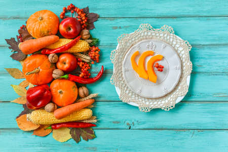 Autumn table setting, menu composition, vintage cutlery, sliced pumpkin. Thanksgiving food, healthy and fresh, top view, flat lay, copy space. Fallen leaves, fruits, vegetables, wooden table. Stock Photo