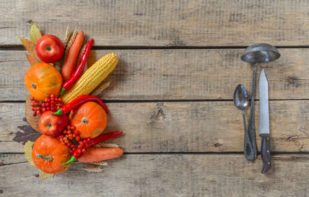 Autumn table setting, menu composition, vintage cutlery. Thanksgiving food, healthy and fresh, top view, flat lay, copy space. Fallen leaves, fruits, vegetables, wooden table.