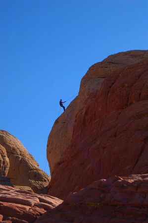 abseiling: A side view of a rockclimber descending from a climb Stock Photo