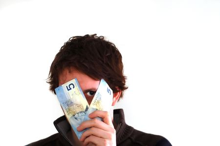 monies: A young male peering from behind two 5 dollar bills Stock Photo