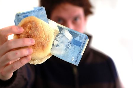 A young man holds up an english muffin with 5 dollar bills inside photo