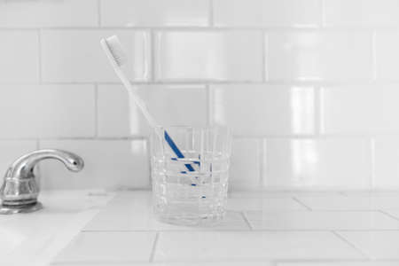 Clean Toothbrush in A Crystal Glass in White Bathroom Stock Photo