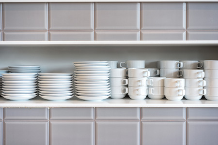 White ceramic coffee cups and saucers on restaurant shelves. Shelves with kitchen utensils. Stock Photo